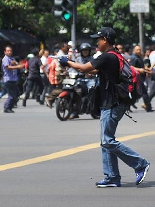 An unidentified man with a gun walks in the street as people run on Thamrin street near S