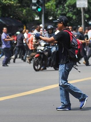 An unidentified man with a gun walks in the street as people run on Thamrin street near Sarinah shopping mall in Jakarta, Indonesia. Picture: AP