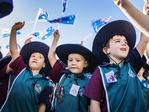 5 year old Talara Primary College Prep students Uenuku Higgins, Knox Lloyd and Archer Bergin wave Australian Flags at the Caloundra Anzac Day Parade. Picture: Lachie Millard