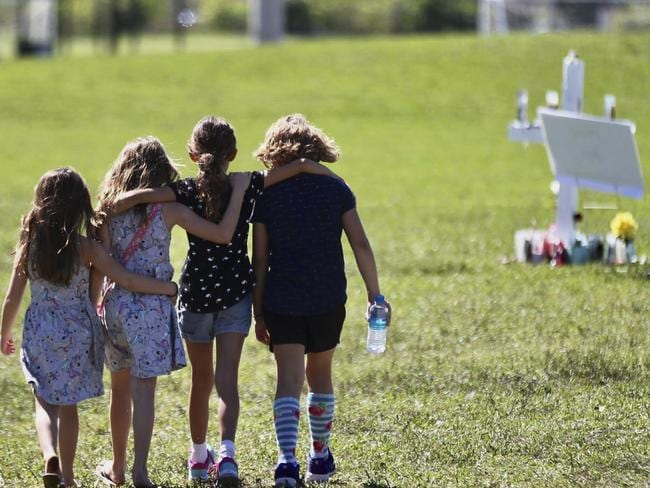 Children approach a vigil post in Parkland, Florida to honour the 17 people who were killed by a former student at Marjory Stoneman Douglas High School. Picture: CM. Guerrero/The Miami Herald/AP