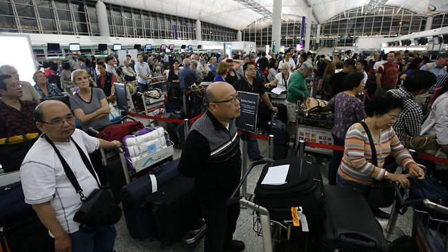 Stranded passengers line up at the Qantas Airways counter for information asking in Hong Kong International Airport. Picture: Kin Cheung / AP