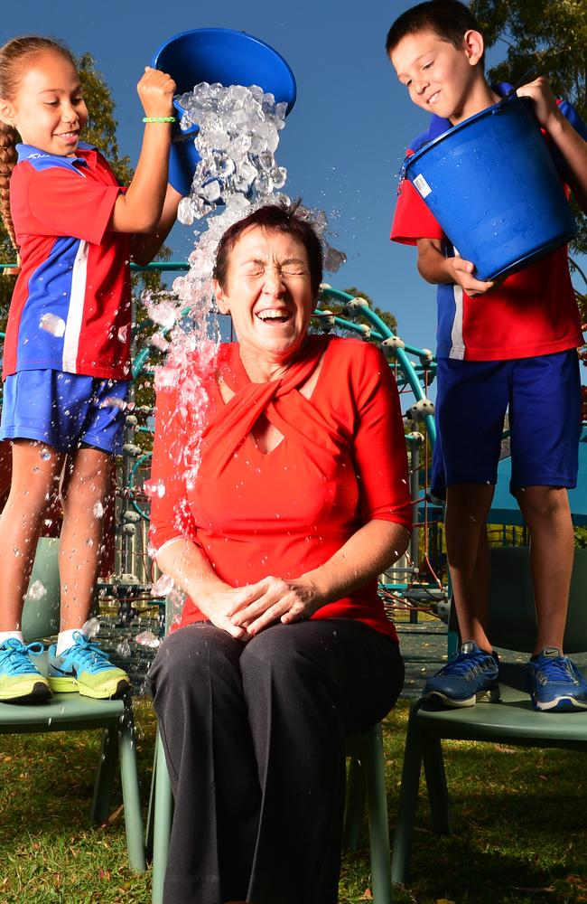 Good cause ... Wulguru State School principal Sandra Perrett took part in the ice bucket challenge as grade 3 students Taleea Gostynski-Leo, 8, and Jack Prior, 9, poured the ice. Picture: Zak Simmonds