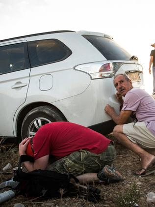 Men take cover behind a car due to a rocket attack siren going off while watching Israeli attacks inside Gaza. Picture: Andrew Burton