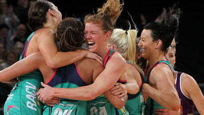 Tegan Caldwell of the Vixens (C) embraces her teammates following victory in the ANZ Championship Grand Final.