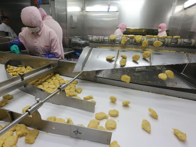 Workers producing food at the Shanghai Husi Food Co. Shanghai city officials have shut a Shanghai Husi factory of US food provider OSI Group for selling out-of-date meat to restaurant giants.