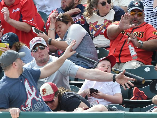 The bat bounces off Cunningham's arm and over his son's head. Picture: Christopher Horner/Tribune-Review