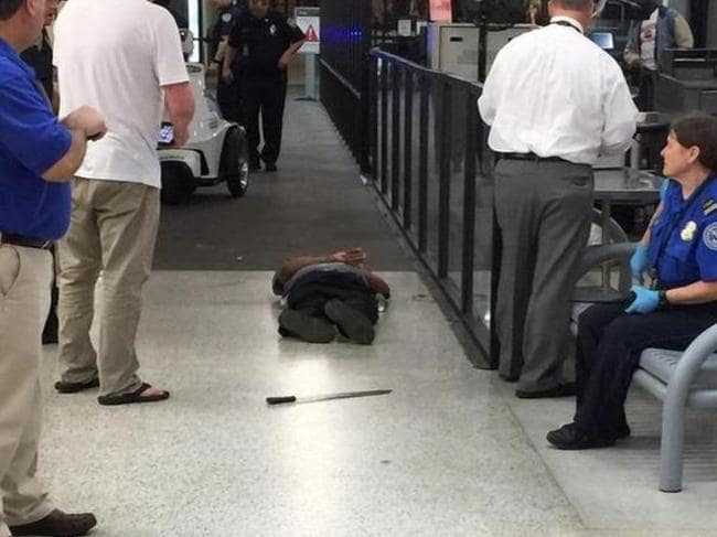 Bag full of explosives and a machete lies on the ground ... Richard White was chasing a TSA employee when he was shot. Source: TWITTER