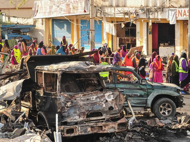 People gather near burnt vehicles a day after a truck bomb exploded outside a hotel at a busy junction in Somalia's capital Mogadishu. Picture: AFP