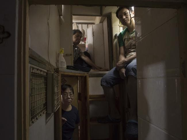 Hong Kong residents, who only gave their surname, Lam, top left, Wan, top right, and Kitty Au are seen sitting in their respective homes. Picture: Kin Cheung/AP
