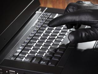 Thief stealing data from a laptop