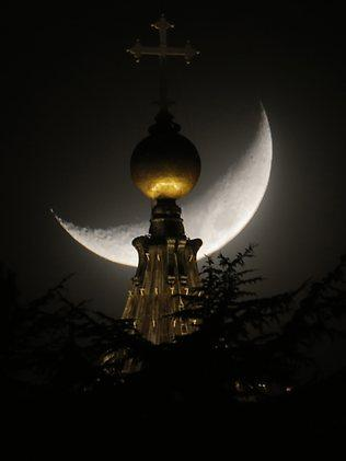 The moon is seen behind a dome of St Peter's Basilica at the Vatican at the weekend. Picture: Dmitry Lovetsky