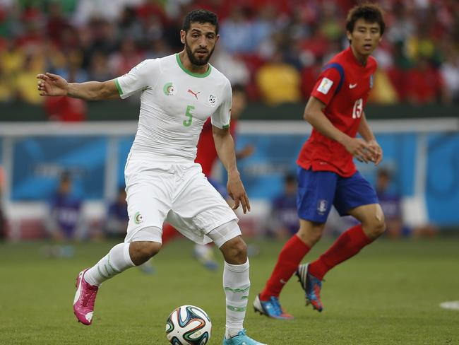 Algerian defender Rafik Halliche controls the ball next to South Korea's forward Koo Ja-Cheol.