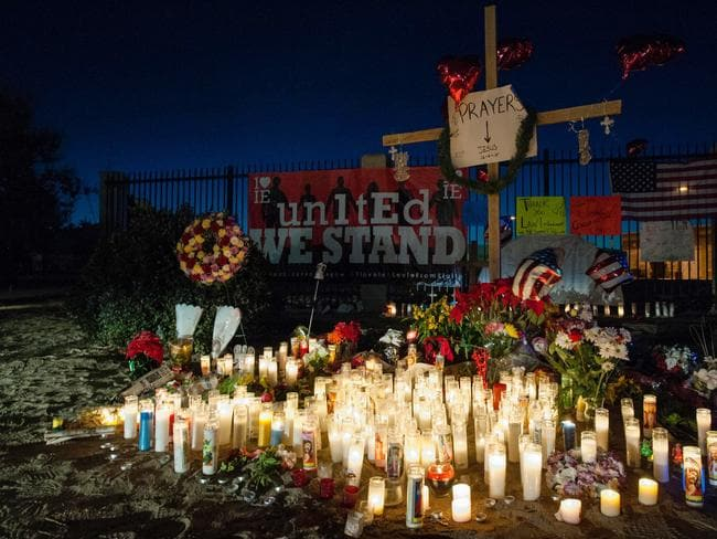 Candles burn ... before dawn at a growing makeshift memorial at Waterman Avenue and Orange Show Road near the Inland Regional Center. Picture: AFP