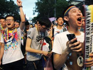Same-sex marriage supporters cheer after the Constitutional Court ruled in favor of same-sex marriage outside the Legislative Yuan in Taipei, Taiwan, Wednesday, May 24, 2017. Taiwan's Constitutional Court ruled in favor of same-sex marriage on Wednesday, making the island the first place in Asia to recognize gay unions. (AP Photo/Chiang Ying-ying)