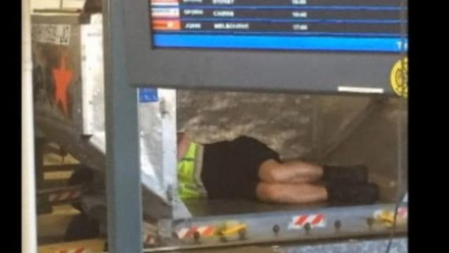 An Aerocare worker sleeps near baggage carousels between shifts. Picture: 7:30