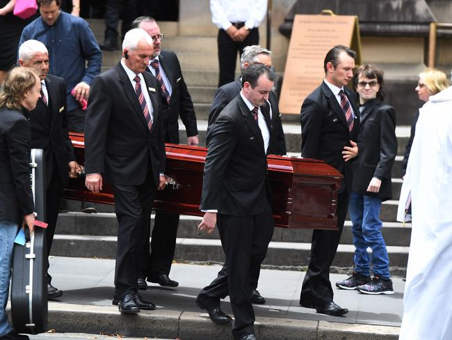 Angus Young, the brother of Malcolm Young, carries a guitar as he watches the casket of his brother Malcolm Young carried from St. Mary's Cathedral. Picture: AAP