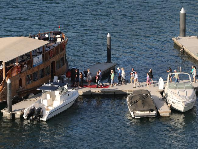 People arrive for a dhow cruise at the Marina water canal.