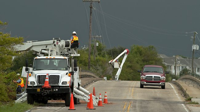 Crews with South Carolina Electric and Gas work to repair power lines that were downed by the first bands of wind and rain from Hurricane Irene overnight. Picture: AP