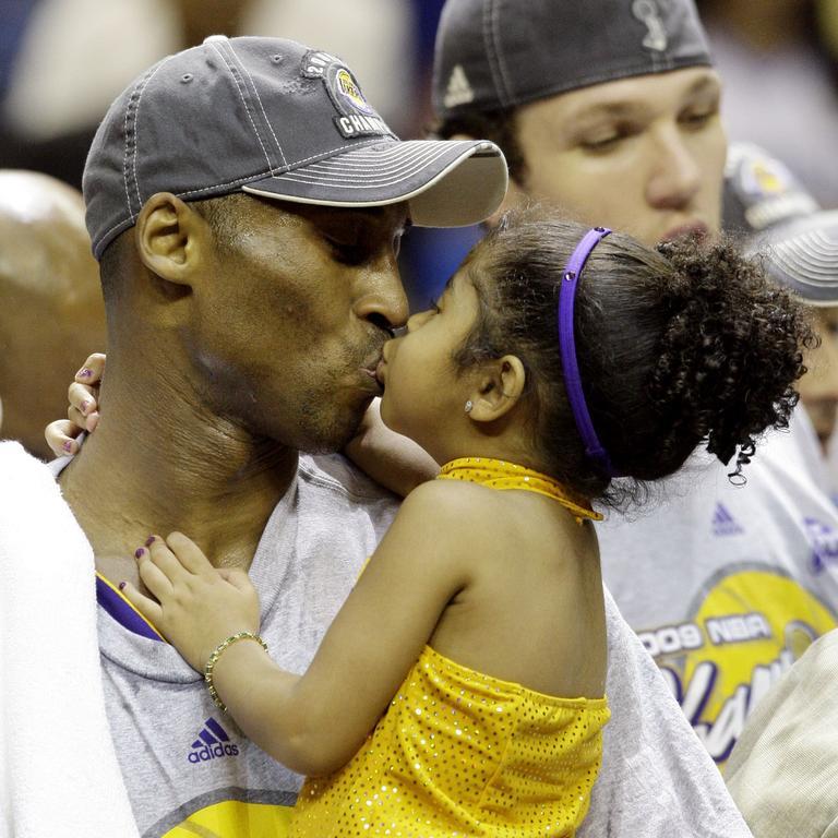 Kobe kisses Gianna after winning an NBA championship in 2009.