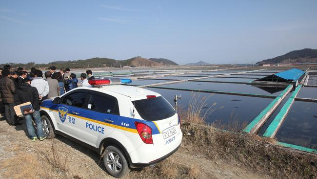 In this Feb. 19, 2014, lawmakers and human right activists look at salt farms as a part of human rights inspection on Sinui Island, South Korea. (AP Photo/Ahn Young-joon)