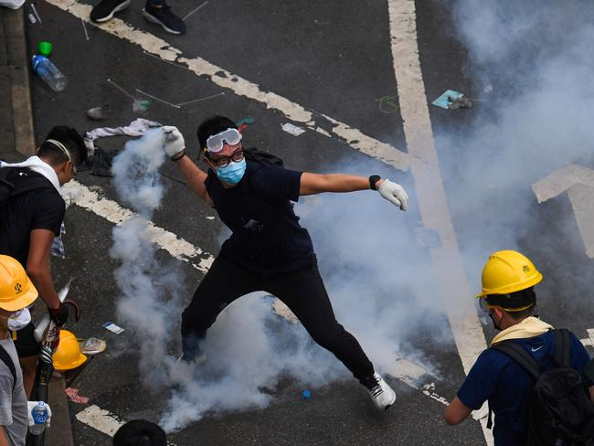 A protester throws back a tear gas during clashes with police outside the government headquarters in Hong Kong on June 12, 2019. Picture: Anthony Wallace/AFP