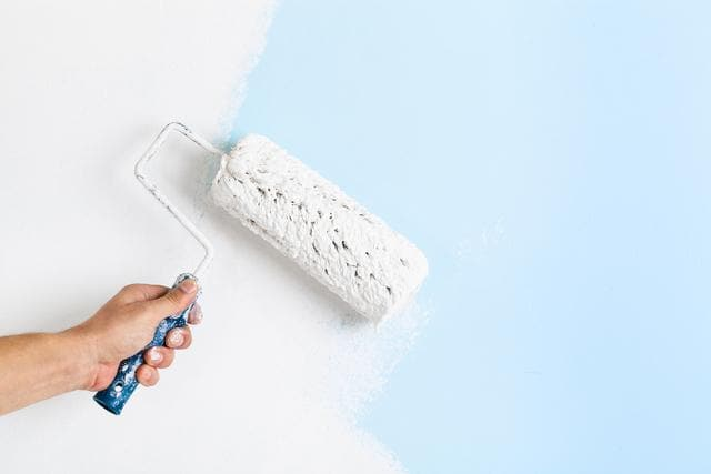 Close up of painter hand painting a wall