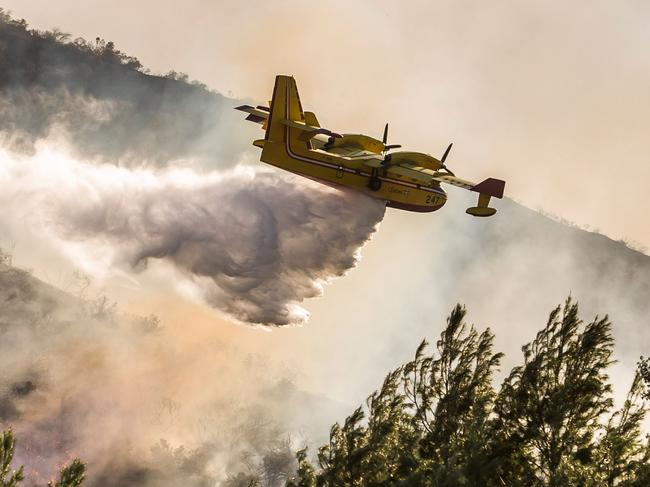 An aeroplane drops water on wildfires close to the 101 Freeway in Thousands Oaks. Picture: AFP