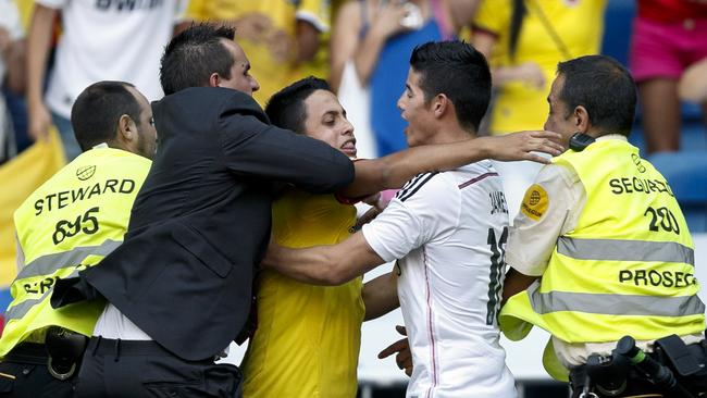 A Colombian fan is grabbed by security guards as he tries to embrace the new Real Madrid player James Rodriguez.