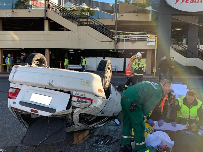 Paramedics at the scene after the car drove off the upper-level carpark. Picture: AAP / SA Police