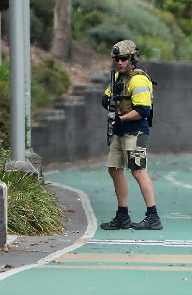 A SERT officer with machine gun guards the bike way along the Brisbane River near the Wesley Hospital, Auchenflower. Photographer: Liam Kidston.