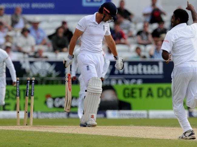 England's Alastair Cook trudges off after being bowled by Dhammika Prasad, right, for 16 runs during day four of the Second Test.