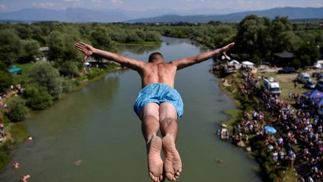 """I'm like a bird … This man jumped from a 22 metre high bridge """"Ura e Shenjte"""" during the annual High Diving competition near the town of Gjakova, Kosovo. Picture: AFP"""