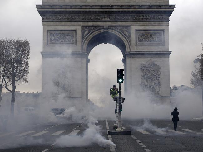 The Arc de Triomphe is pictured in a cloud of tear gas during clashes between demonstrators, called the yellow jackets, and riot police. Picture: AP Photo/Kamil Zihnioglu