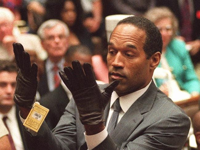 "O.J. Simpson holds up his hands after putting on a new pair of gloves similar to the infamous ""bloody gloves"" during his double-murder trial in June 1995. The key moment in court sough to underscore that the gloves found at the murder scecen did not fit. Picture: AP"