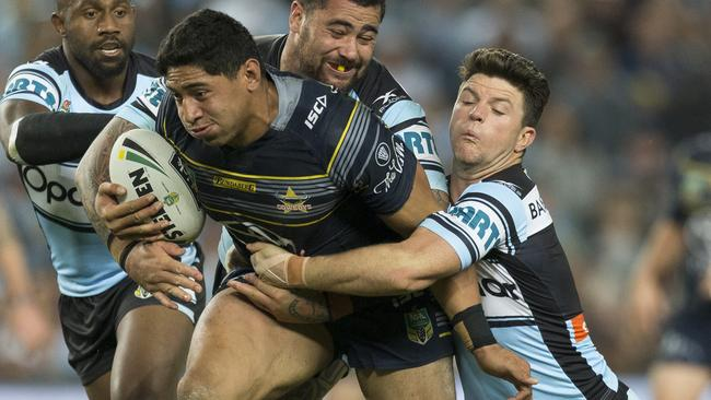 Jason Taumalolo of the Cowboys is tackled by Andrew Fifita and Chad Townsend of the Sharks.