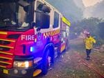 An out of control fire ripped through the Blue Mountains this afternoon. Unknown houses and other property has been destroyed along Bells Line of Road from Bilpin to Mount Tomah and further west. Firefighters rush to protect a burning industrial shed full of burning plastics. Picture: Matrix