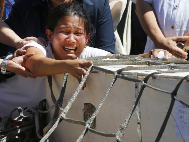 Jessica Demafelis, the sister of Joanna Demafelis who was found dead in a freezer in Kuwait, crying over the wooden casket of her remains. Photo: AP Photo/Bullit Marquez