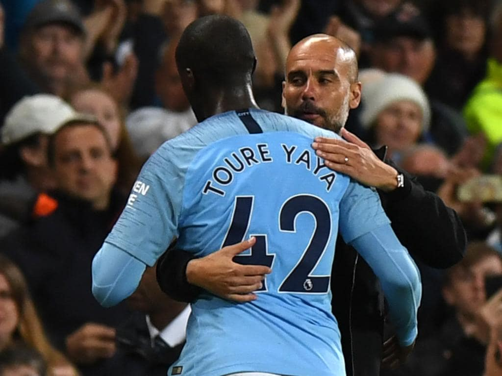 """(FILES) In this file photo taken on May 09, 2018 Manchester City's Spanish manager Pep Guardiola (R) embraces Manchester City's Ivorian midfielder Yaya Toure as he is substituted during the English Premier League football match between Manchester City and Brighton and Hove Albion at the Etihad Stadium in Manchester, north west England. Manchester City manager Pep Guardiola has hit back at Yaya Toure denying accusations he's racist in an interview on Spanish television. Ivorian international midfielder Toure had told France Football magazine earlier this week that he had questioned whether his skin """"colour"""" had contributed to him being little used by Guardiola during City's record breaking run to the Premier League title last season. / AFP PHOTO / Paul ELLIS / RESTRICTED TO EDITORIAL USE. No use with unauthorized audio, video, data, fixture lists, club/league logos or 'live' services. Online in-match use limited to 75 images, no video emulation. No use in betting, games or single club/league/player publications.  /"""