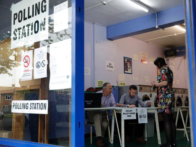 A presiding officer and poll clerk greet an early morning voter at a polling station in a laundrette in Headington outside Oxford.