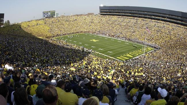 Football fans attend the University of Michigan versus Michigan State game at Michigan Stadium.