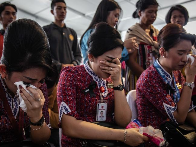 Families and colleagues of victims of Lion Air flight JT 610 cry on deck of Indonesian Navy ship KRI Banjarmasin during visit and pray at the site of the crash. Picture: Getty