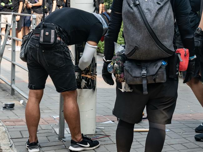 Protester cut a smart lamppost during the anti-government rally. Picture: Anthony Kwan/Getty Images