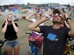 The Bariclow family watches the first solar eclipse to sweep across the United States in over 99 years on the beach August 21, 2017 on Hilton Head Island, South Carolina. Picture: Win McNamee/Getty Images/AFP