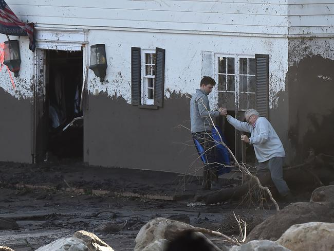 A man tries to enter his mud-damaged home in Montecito. Picture: AFP/Robyn Beck