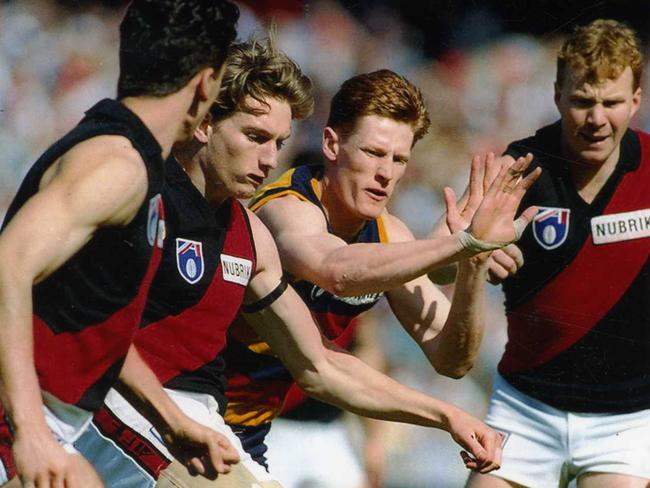 Adelaide's Ben Hart attempts to smother a kick by James Hird.