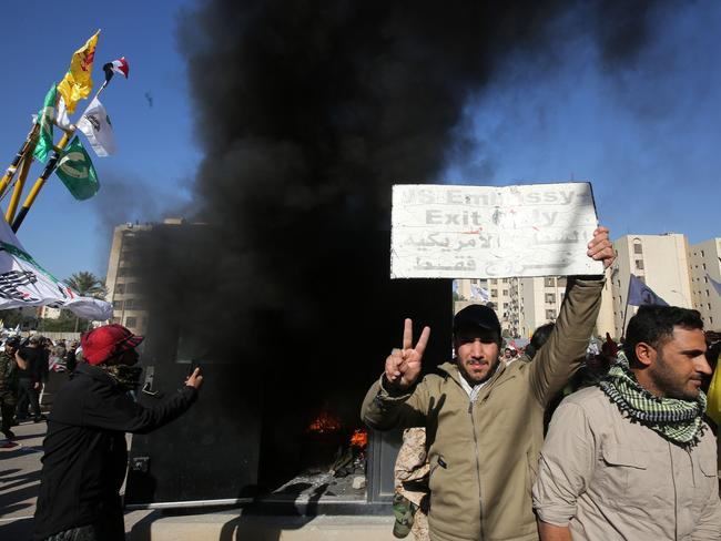 An Iraqi protester holds up a sign that was detached from the US embassy wall as a sentry box is set ablaze in front of the building in the capital Baghdad. Picture: AFP