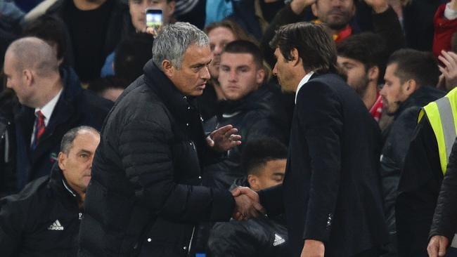 Manchester United's Portuguese manager Jose Mourinho (L) shakes hands with Chelsea's Italian head coach Antonio Conte