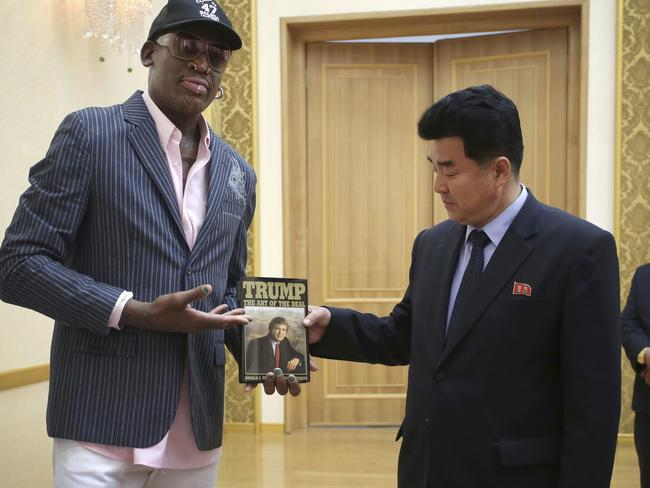Former NBA basketball star Dennis Rodman presents Donald Trump's The Art of the Deal to North Korea's Sports Minister Kim Il-guk in Pyongyang. Picture: AP Photo/Kim Kwang Hyon