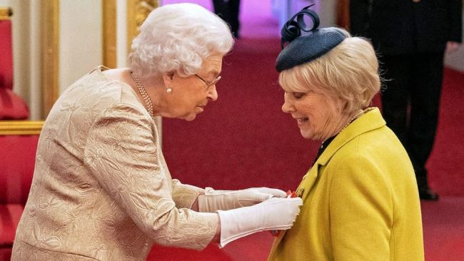 Queen Elizabeth wears gloves as she awards the CBE to actress Wendy Craig. Image: Dominic Lipinski/PA via AP.