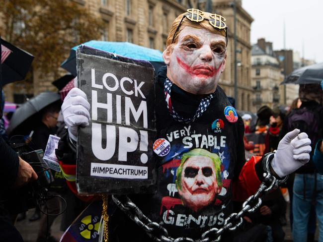 A man dressed up as the movie character 'the joker' with the hair style of the US President Donald Trump, holds a sign during an protest against the US leader at the Place de la Republique in central Paris. Picture: AFP